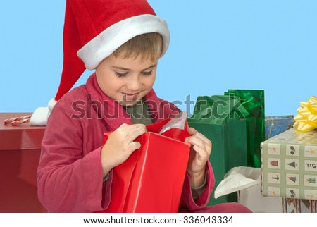 Boy in Bathrobe and Santa Hat Opening a Red Wrapped Christmas Present - stock photo
