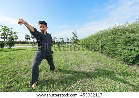 Boy in black kimono during training karate kata exercises in park