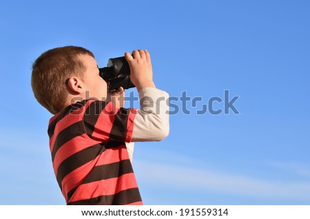 Boy in black-red t-shirt exploring the clear blue sky through binoculars.