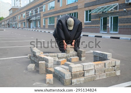 boy in black suit inflatable building brick wall in parking lot near apartment house