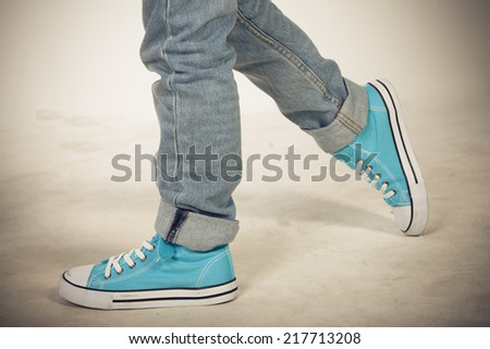 Boy in blue sneakers walking - stock photo
