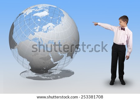 Boy in bow tie points a finger at a translucent globe on a blue background. Elements of this image furnished by NASA - stock photo