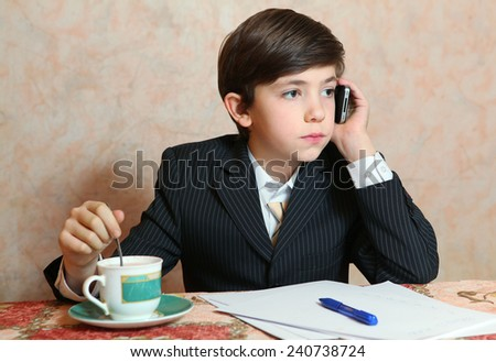 boy in businessman suit talking on cell phone - stock photo