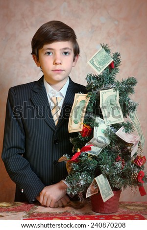 boy in businessman suit with christmas tree and money - stock photo