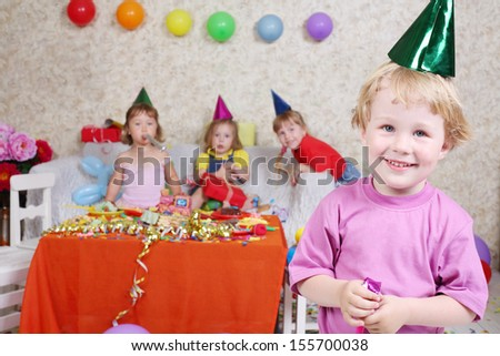 Boy in cap and with party blowers smiles at birthday party and three girls sit on couch. Inscription Happy Birthday on wall. Focus on boy. - stock photo