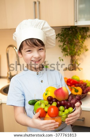 Boy in cap chef in the kitchen holding a bowl of vegetables and fruits and smiling.