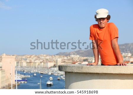 Boy in cap poses on concrete wall on hill with views of old port Marseille, France