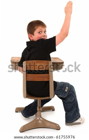 Boy in casual clothes sitting in school desk hand raised over white background. - stock photo