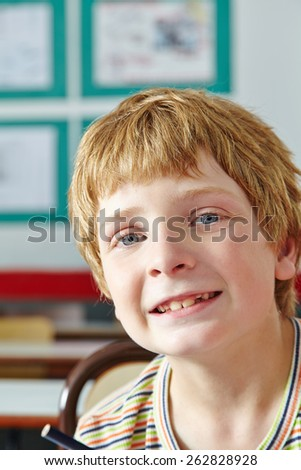 Boy in classroom of elementary school smiling into the camera - stock photo