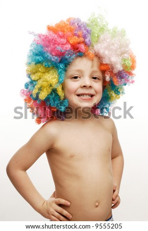 Boy in colorful bright wig standing his hands on his hips - stock photo