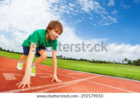 Boy in colorful uniform on the start ready to run - stock photo