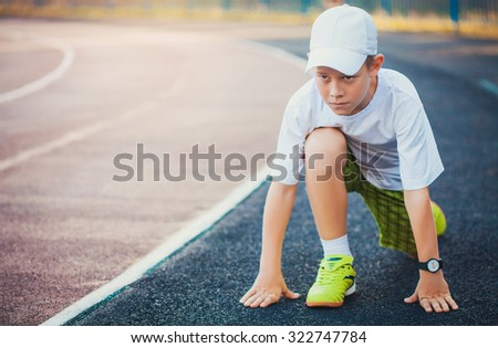 Boy in colorful uniform on the start ready to run