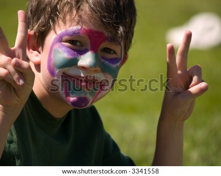 Boy in face paint gives the peace sign.