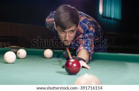 boy in focus aiming for shot the billiard ball which aren't in focus - stock photo