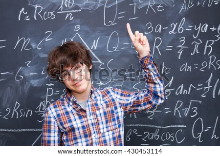 Boy in glasses, blackboard filled with math formulas background - stock photo