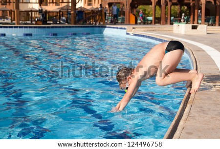 Boy in glasses jumping into the pool - stock photo