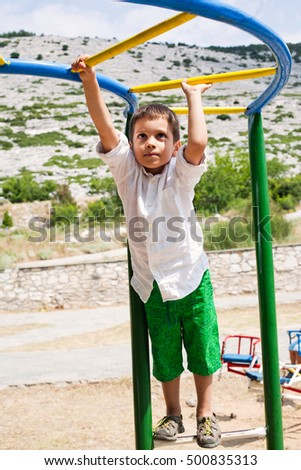 Boy in green shorts and white shirt playing on jungle gym at playground on sunny day.