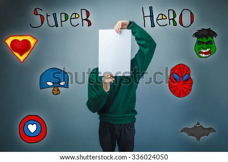 boy in green sweater holding a face sheet of clean paper superhero super power of the photo studio Icons hero - stock photo