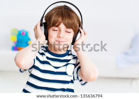 boy in headphones enjoys music, Keep your hands on the headphones - stock photo