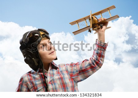 Boy in helmet pilot playing with a toy wooden airplane in the clouds, dreaming of becoming a pilot - stock photo