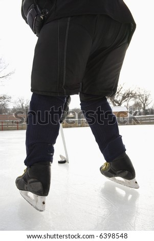 Boy in ice hockey uniform skating on ice rink moving puck. - stock photo