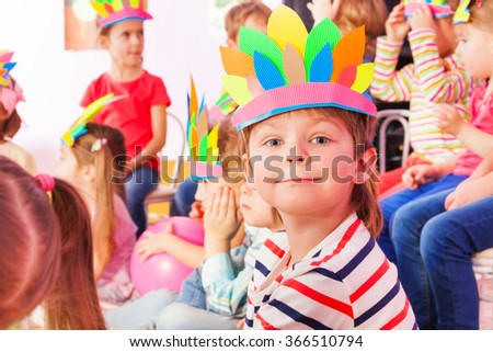 Boy in Indian headwear with group of kids