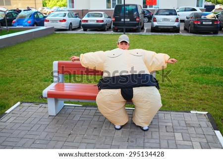 Boy in inflatable sumo wrestler suit sitting on bench on territory near house