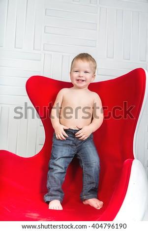 Boy in jeans smiles - stock photo