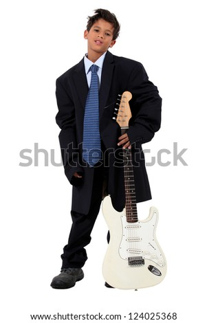 Boy in loose fitting suit stood with electric guitar - stock photo