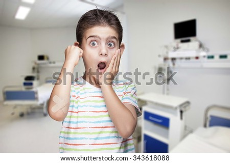 Boy in pain with wounded arm at a hospital room. Image with shallow depth of field - stock photo