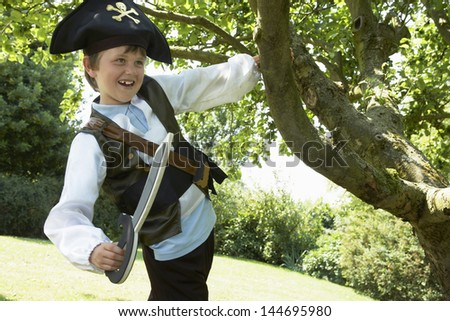Boy in pirate costume swinging from tree in the park - stock photo