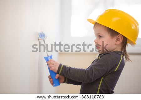 boy in protective helmet painted the wall