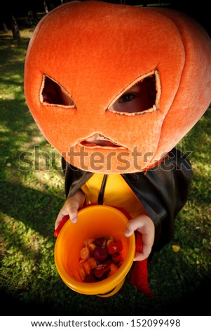 Boy in pumpkin hat trick or treating.Shot with wide-angle lens effect - stock photo