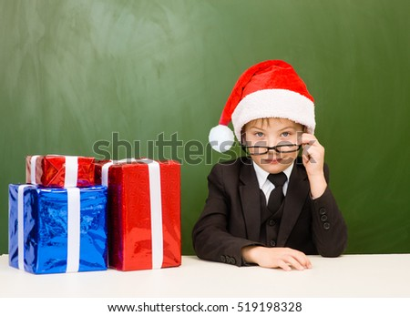 Boy in red christmas hat with gift boxes near empty green blackboard.
