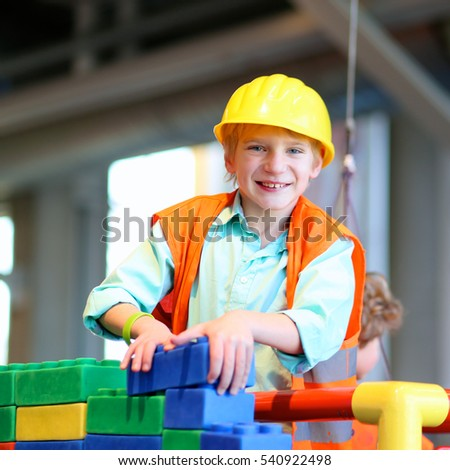 Boy in safety helmet and high visibility jacket plays indoors. Schoolchild building house with plastic construction bricks. Safety education for small children. Playful work experience for young kids.