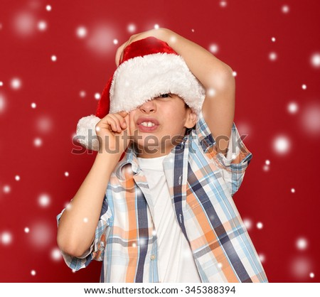 boy in santa hat close one eye on red with snow
