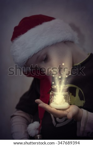 Boy in Santa's hat with glittering surprise, New Year concept - stock photo