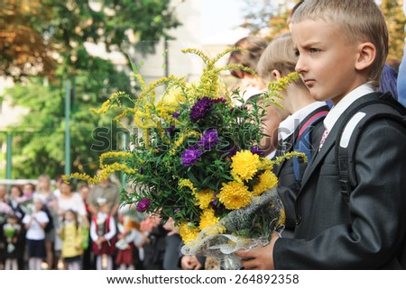 Boy in school uniform and satchel goes to school for the first time, on school holidays - stock photo