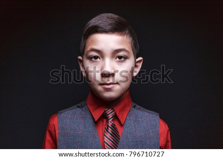 Boy in serious looking portrait wearing a nice suit vest with a tie.