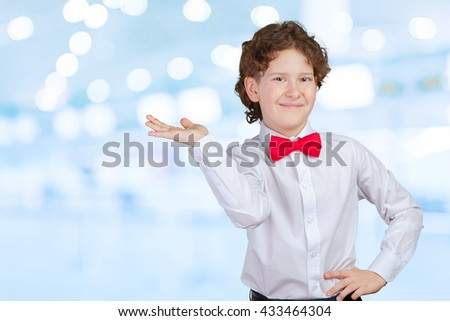 Boy in shirt pointing with his palm - stock photo
