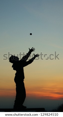 Boy in silhouette against sunset sky, throwing a ball up and reaching to catch it, orange sky background.