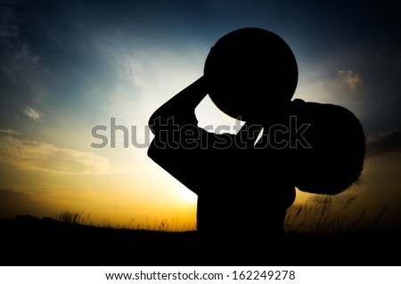 Boy in silhouttee kiss the ball during sunset  - stock photo