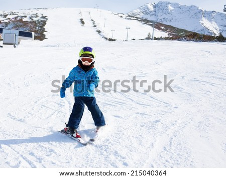 Boy in ski mask learns skiing on snow downhill of the mountain - stock photo