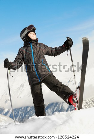 Boy in ski suit stands rising up one leg with ski and looking upward, blue sky and mountains on background - stock photo