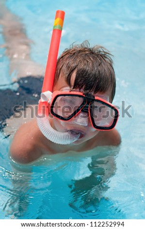 Boy in snorkeling mask with snorkel in pool at aqua park - stock photo