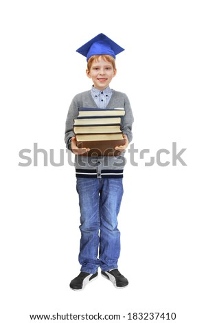 Boy in square academic cap stands with stack of books in hands. Isolated on white background - stock photo