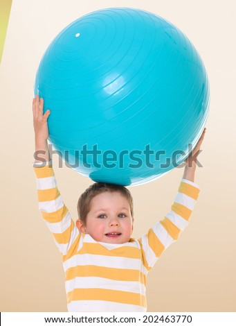boy in striped shirt holding big ball over his head.passionate child for interesting occupation,active lifestyle,happiness concept,carefree childhood concept. - stock photo