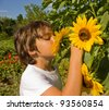 boy in summer colorful garden sniffing sunflower - stock photo