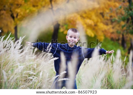 boy in the autumn meadow - stock photo