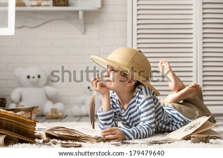 Boy in the image traveler studying his book of travel and adventure in her room - stock photo